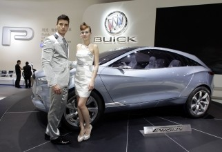 Models stand next to the Buick Envision SUV concept car at Auto China 2012 in Beijing