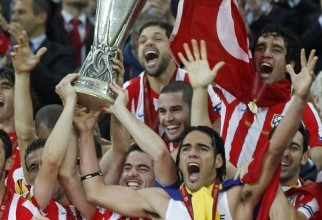 Atletico Madrid's players celebrate with the trophy after defeating Athletic Bilbao to win the Europa League final soccer match at the National Arena in Bucharest