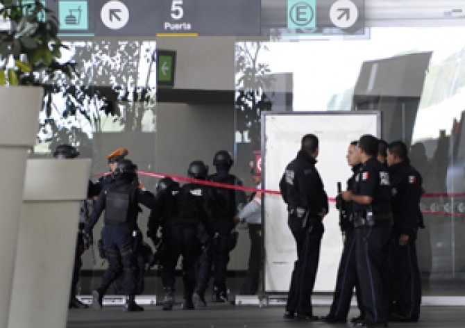 Federal police officers arrive where federal policemen were killed in a shooting at the airport in Mexico City