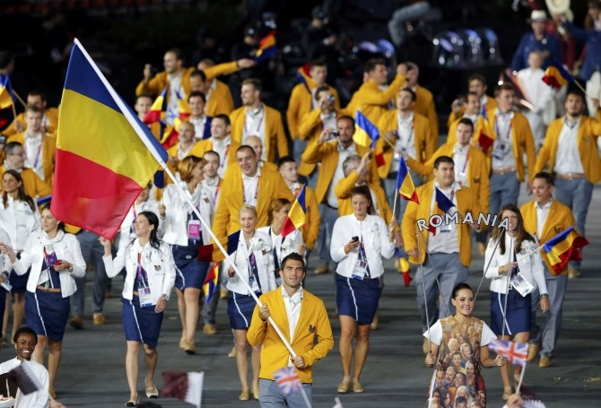 Romania's flag bearer Horia Tecau holds the national flag as he leads the contingent in the athletes parade during the opening ceremony of the London 2012 Olympic Games at the Olympic Stadium
