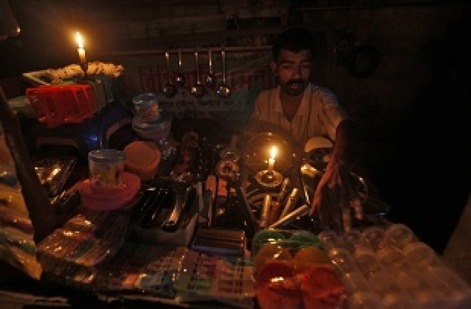 A gas oven mechanic waits for customers in his shop during a power-cut in Kolkata