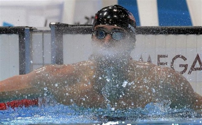Michael Phelps of the U.S. spits out water after winning the men's 100m butterfly final during the London 2012 Olympic Games at the Aquatics Centre