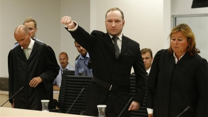 Norwegian mass killer Breivik gestures as he arrives in the court room at Oslo Courthouse
