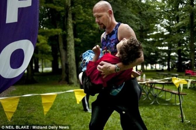 """""""Tatăl secolului"""": Un bărbat aleargă la triatlon cu fiica lui bolnavă în braţe"""