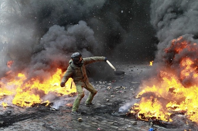 A demonstrator throws a stone amid burning tyres set ablaze by pro-European protesters during clashes with riot police in Kiev