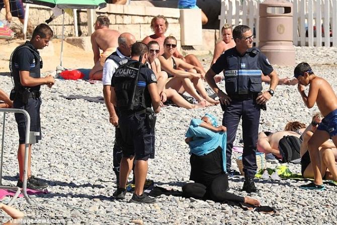 Patru poliţişti francezi înarmaţi în timp ce pun în aplicare legea care interzice purtarea burkini pe o plaje în apropiere de Promenade des Anglais, unde 86 de persoane şi-au pierdut viaţa în urmă cu mai bine de o lună.