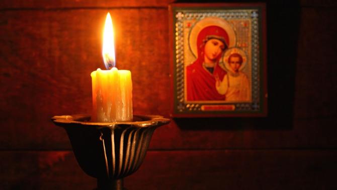 Lumânare aprinsă la icoana Maicii Domnului