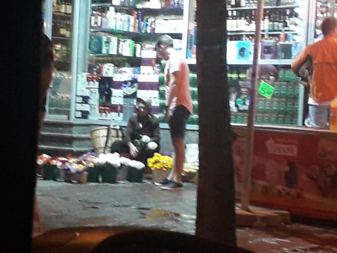 Un tânăr cumpără flori de la bătrâna care și-a apărat munca