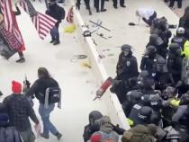 Imaginea care arată momentul în care un stingător este aruncat spre ofițeri. Un ofițer este lovit în cap. Sursă foto: Captură video Youtube Inside Edition