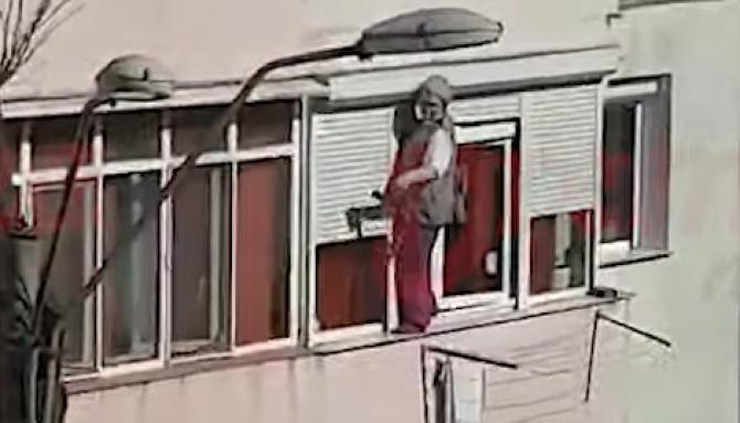 O femeie a ieșit pe pervazul exterior al geamului ca să-l șteargă, la etajul 2 / Sursă foto: Captură Youtube VremeaNoua