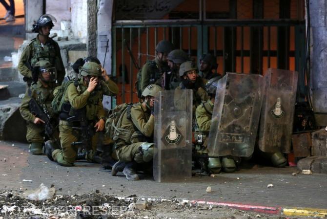 Trupele israeliene sunt văzute în timpul ciocnirilor cu protestatarii palestinieni în centrul orașului Hebron din Cisiordania, 12 mai 2021.