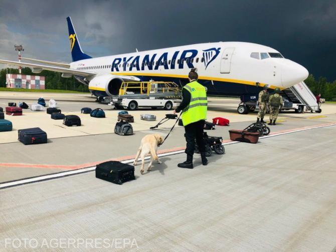 Securitatea aeroportului  verifică bagajele pasagerilor în fața aeronavei Ryanair