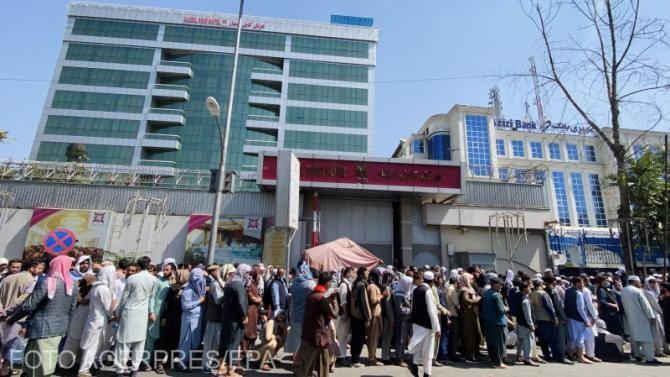 Oamenii se aliniază pentru a retrage bani de la bănci, deoarece băncile au permis retragerea de 200 USD pe săptămână dintr-un cont la sucursalele lor centrale din Kabul.