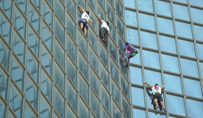 """""""Omul Păianjen"""" francez și trei """"ucenici"""" s-au cățărat pe un turn din Franța, ca protest la certificatul COVID-19   /  Sursă foto: Captură YouTube Global News"""